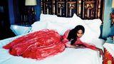Naomi Campbell liegt im Ballkleid auf einem Hotelbett
