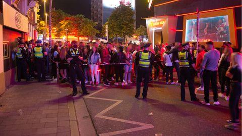 Dutzende Menschen stehen dicht beieinander an dem von der Polizei gesperrten Eingang zur Großen Freiheit