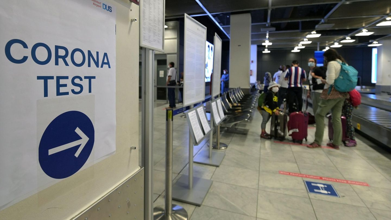 Ein Schild am Flughafen Düsseldorf weist zu einer Corona-Teststelle