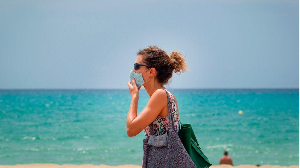 Touristin mit Maske an der Platja de Palma