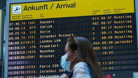 Berlin: Vor der Ankunfts-Anzeigetafel geht eine Reisende mit Mundschutz durch den Flughafen Tegel