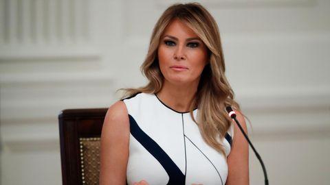 Melania Trump sitzt vor einem Mikrofon an einem Tisch