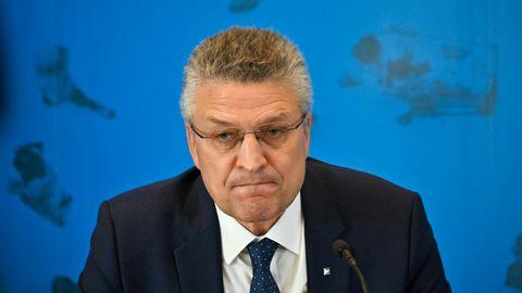 Ein Mann mit grau melierten Locken und randloser Brille sitzt in Anzug und Krawatte vor einer blauen Wand mit Weltkarte