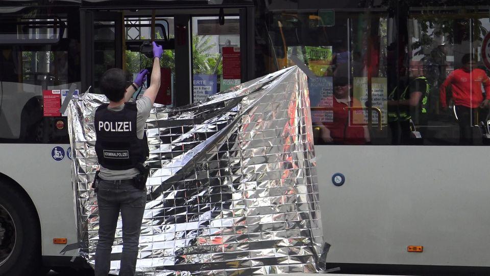 Ein Mitarbeiter der Kriminalpolizei fotografiert den Tatort einer Messerattacke in einem Linienbus.