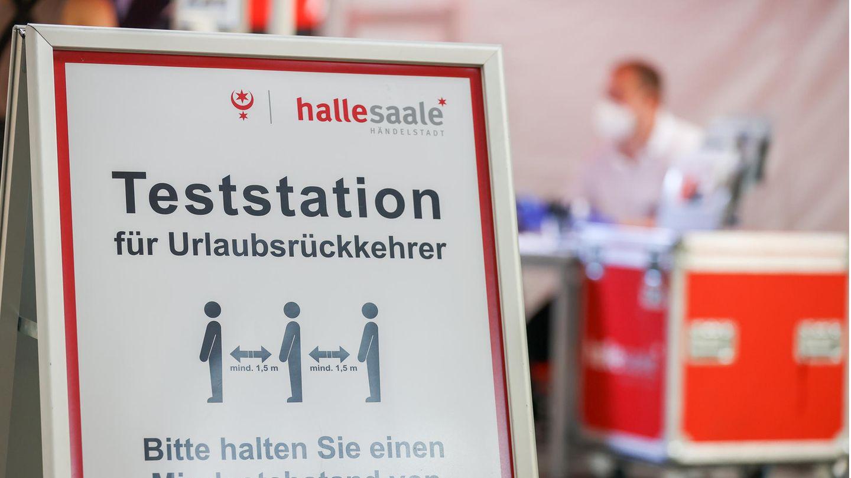 Ein Schild weist den Weg zur Corona-Teststation am Flughafen Leipzig/Halle