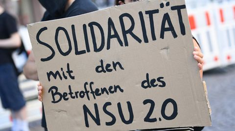 """Eine junge Demonstrantin hält ein Pappschild mit """"Solidarität mit den Betroffenen des NSU 2.0"""""""