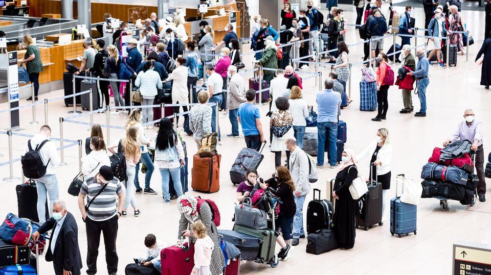 Flugpassagiere mit Mund-Nasen-Schutzmasken stehen an Check-in Schaltern des Flughafens Hamburg