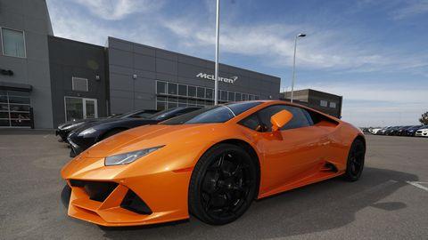 Ein orangefarbener Sportwagen steht als vorderster in einer ganzen Reihe ähnlicher Autos