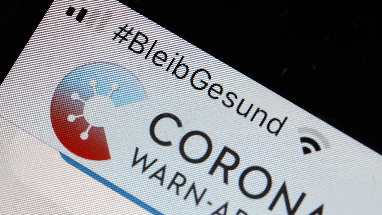 Die Corona-Warn-App mit der Seite zur Risiko-Ermittlung ist im Display eines Smartphone zu sehen
