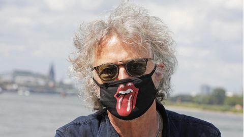 """Ein Mann mit grauer Lockenmähne trägt eine Sonnenbrille und einen Mund-Nase-Schutz mit dem Logo der """"Rolling Stones"""""""
