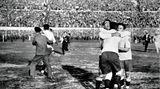 30. Juli 1930: Uruguay gewinnt 4:2 gegen Argentinien–und wird erster Fußball-Weltmeister  Die uruguayischen Fußball-Nationalspieler (von rechts) Hector Scarone, Enrique Ballestero und Hector Castro freuen sich am 30. Juli 1930 im Estadio Centenario in Montevideo, Uruguay, über die gewonnene Fußball-Weltmeisterschaft nach dem Endspiel gegen Argentinien. Uruguay ist damit erster Fußballweltmeister.Viele argentinischen Schlachtenbummler bekommen die Niederlage aber gar nicht mit: Sie sitzen auf Schiffen auf dem Río de la Plata fest, die wegen des dichten Nebels nicht anlegen können.  Weil Schiedsrichter John Langenus befürchtet, dass bei der Partie zwischen den Erzrivalen Argentinien und Uruguay die Emotionen hochkochen, verlangt er strenge Waffenkontrollen. Und tatsächlich werden vor dem Anpfiff rund 1600 Revolver von den Zuschauern eingesammelt. Trotzdem geht der Unparteiische auf Nummer sicher: Im Hafen wartet ein Boot, um ihn notfalls in Sicherheit zu bringen.
