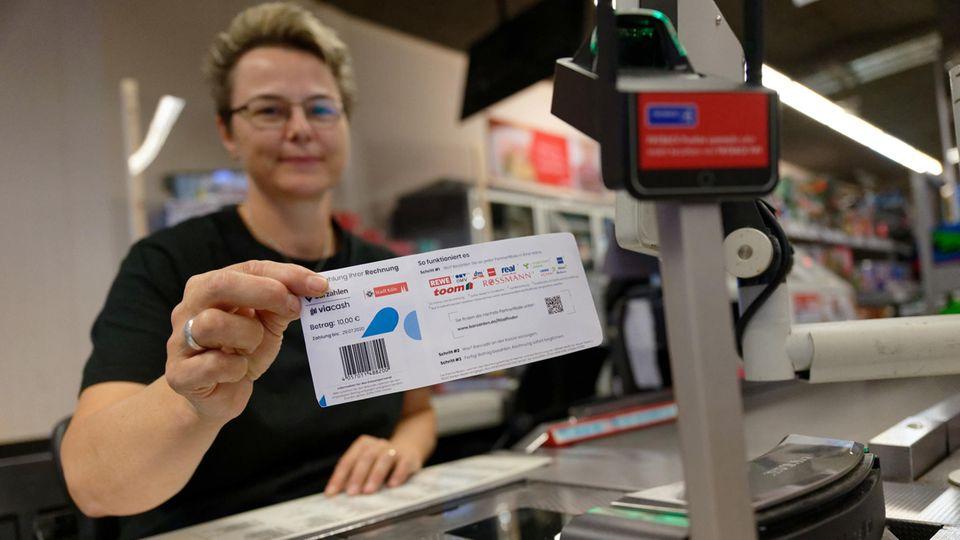 Mitarbeiterin einer Rewe-Filiale in Köln zeigt Knöllchen-Abschnitt mit Barcode