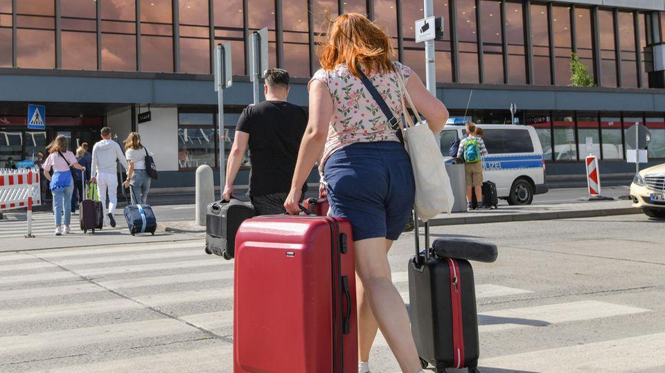Reisende gehen mit Koffern zum Terminal des Flughafens Berlin Schönefeld.