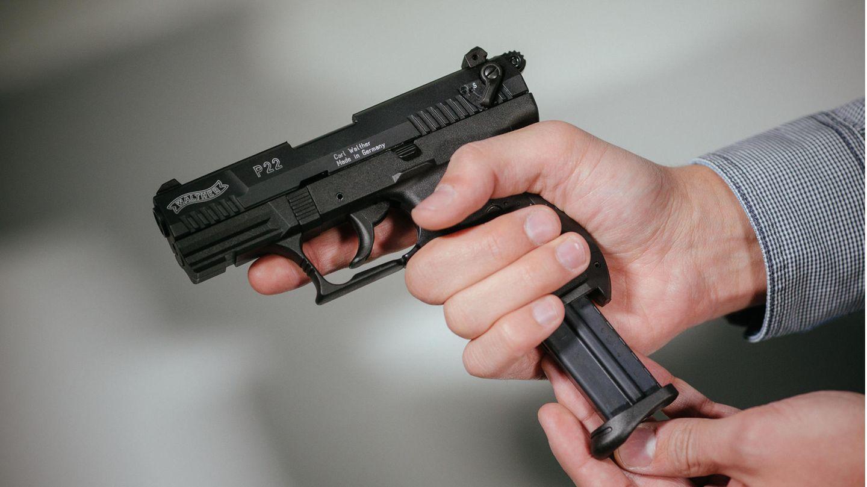 """Hände laden eine Schreckschuss-Pistole """"Walther P22"""" mit einem Magazin"""