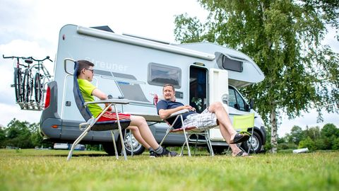 Zwei junge Männer sitzen in legerer Kleidung in Campingstühlen vor einem Wohnmobil
