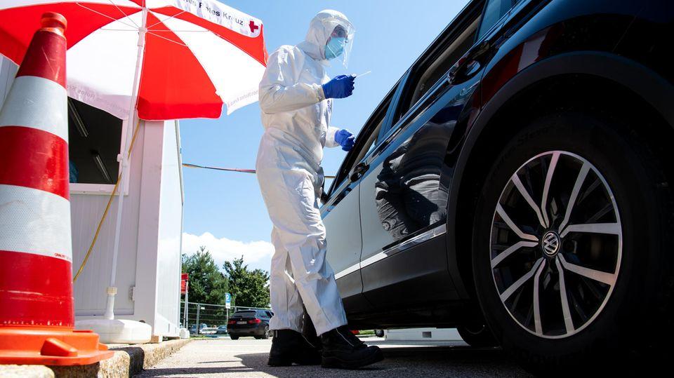 Mitarbeiter vom Bayerischen Roten Kreuz nehmen an einem Corona-Testzentrum einen Abstrich