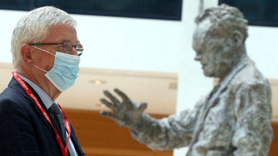Buchautor Thilo Sarrazin mit Schutzmaske vor der Statue von Willy Brandt in der SPD-Zentrale