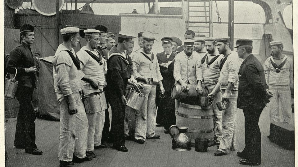 """Matrosen der Royal Navy erhalten eine Tagesration Rum. Die Aufnahme stammt aus dem Jahr 1895 - an die Abschaffung des """"Tot"""" war damals noch nicht zu denken."""