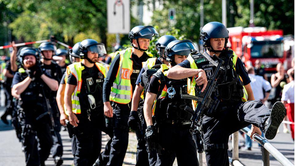 Schwer bewaffnete Polizeibeamte stehen an einem Kaufhaus am Hermannplatz
