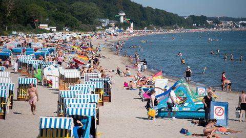 Schleswig-Holstein, Timmendorfer Strand: Zahlreiche Menschen sind schon in den Morgenstunden am Ostseestrand unterwegs