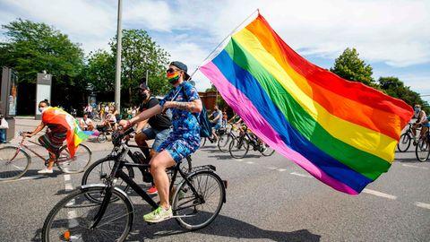 CSD 2020: Ein Demonstrant fährt mit dem Rad und einer Regenbogenfahne durch Hamburg.