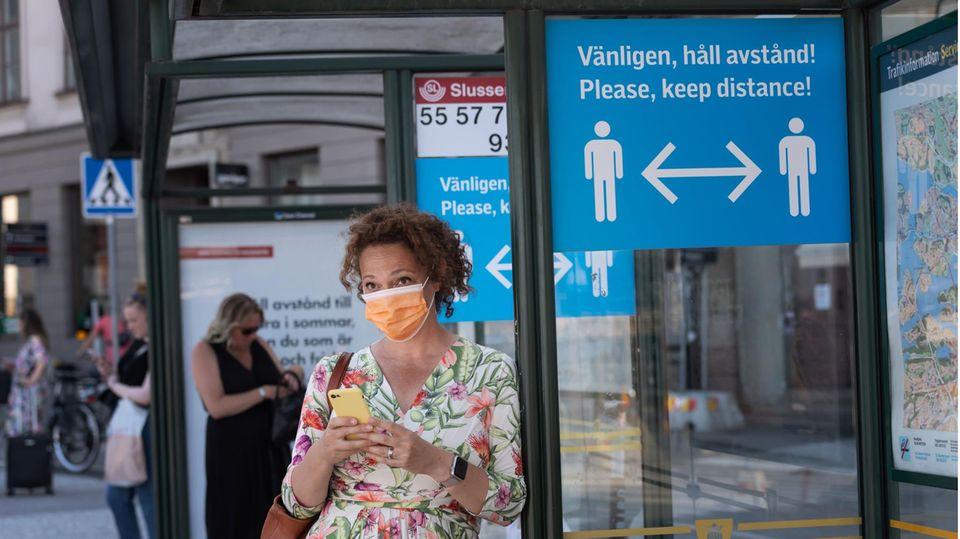 Eine Frau mit Mund-Nase-Schutz wartet an einer Bushaltestelle in Stockholm. Ein Schild weist auf Abstandsregeln hin.