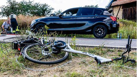 Ein Fahrrad liegt am Seitenstreifen einer Straße.