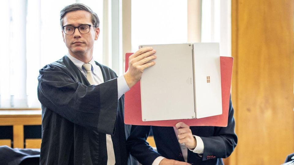 Essen: Der Angeklagte (r) steht im Gerichtssaal mit einer Mappe vor dem Gesicht neben seinem Anwalt Roland Rautenberger