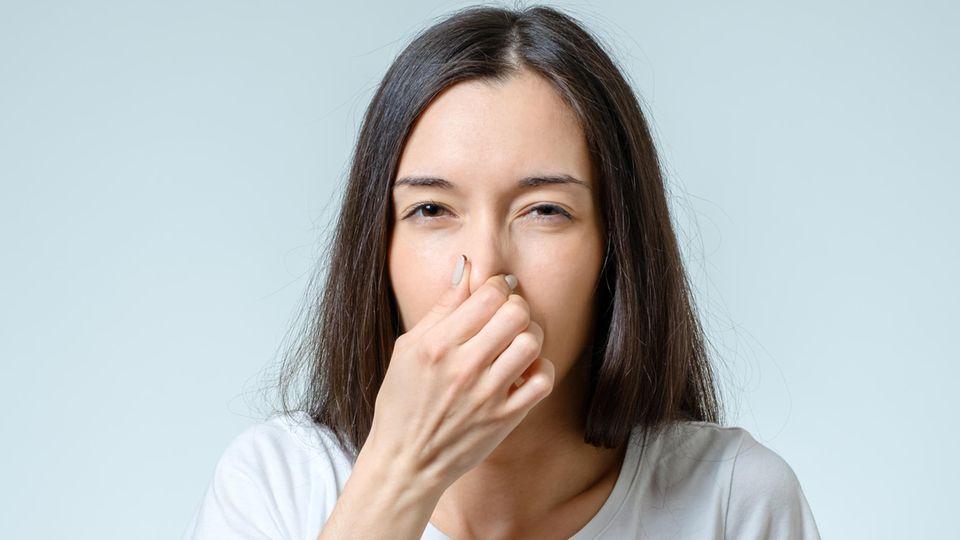 Coronavirus Anosmie: Eine Frau hält sich die Nase zu