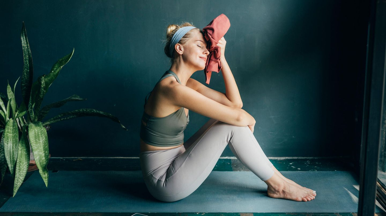 Corona Fitnessstudio: Eine Frau macht Yoga im eigenen Zuhause