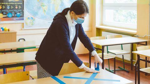 Eine Lehrerin klebt Tische ab