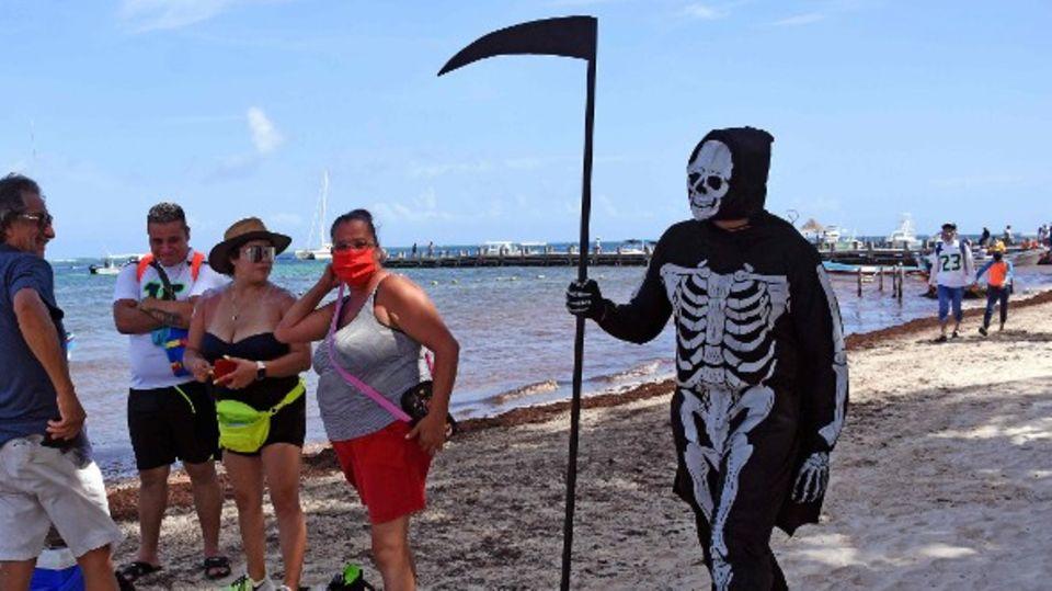 Mann verkleidet sich als Sensenmann am Strand