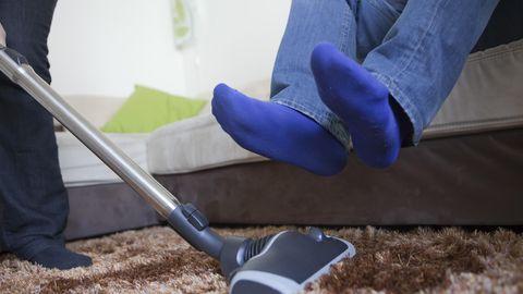 Ein Mann hebt seine Beine, während eine Frau den Teppich saugt