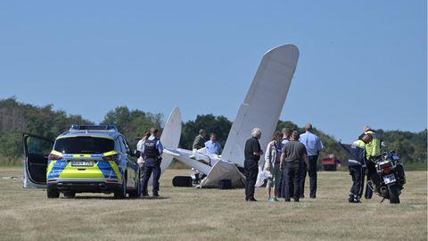 Rettungskräfte stehen am Flughafen Iserlohn-Rheinermark an der Stelle, an der ein Leichtflugzeug abgestürzt ist