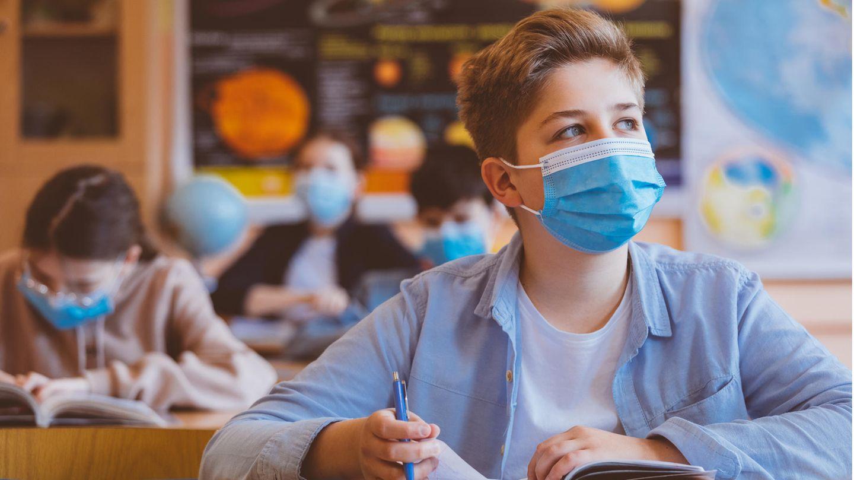 Kinder sitzen mit Mund-Nasen-Schutz im Unterricht