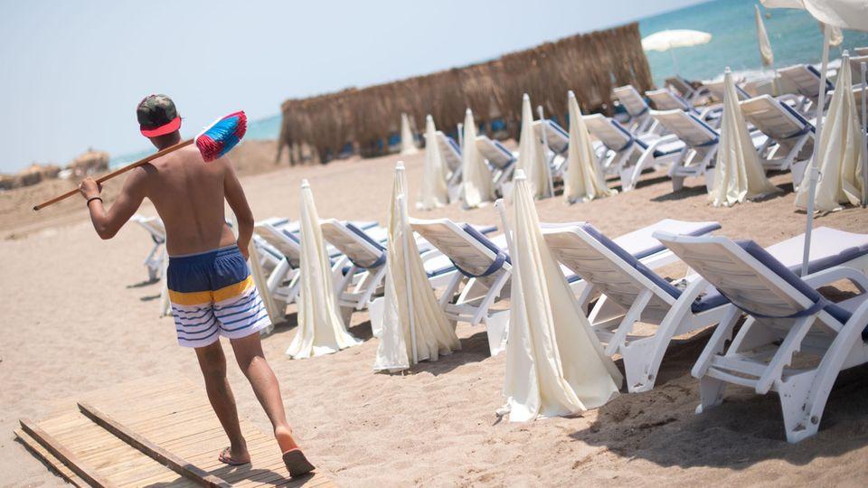 Ein Mann mit einem Besen geht an einem leeren Strand in Antalya (Türkei) entlang