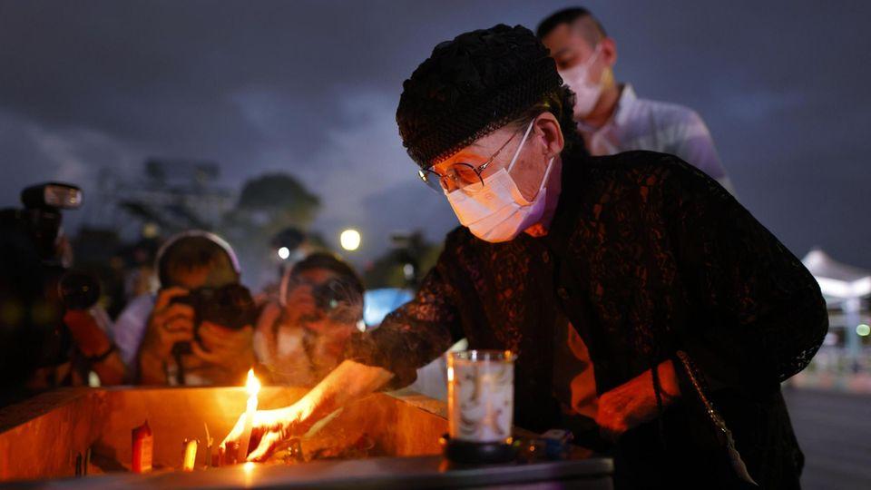 Eine Frau entzündet am Ehrengrabmal für die Hiroshima-Opfer eine Kerze