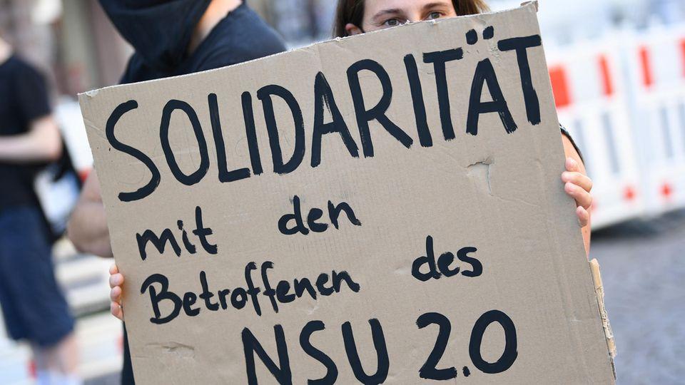 """Ein Demonstrantin fordert während einer Kundgebung in Wiesbaden auf einem Plakat """"Solidarität"""" für die Opfer der Drohmails"""