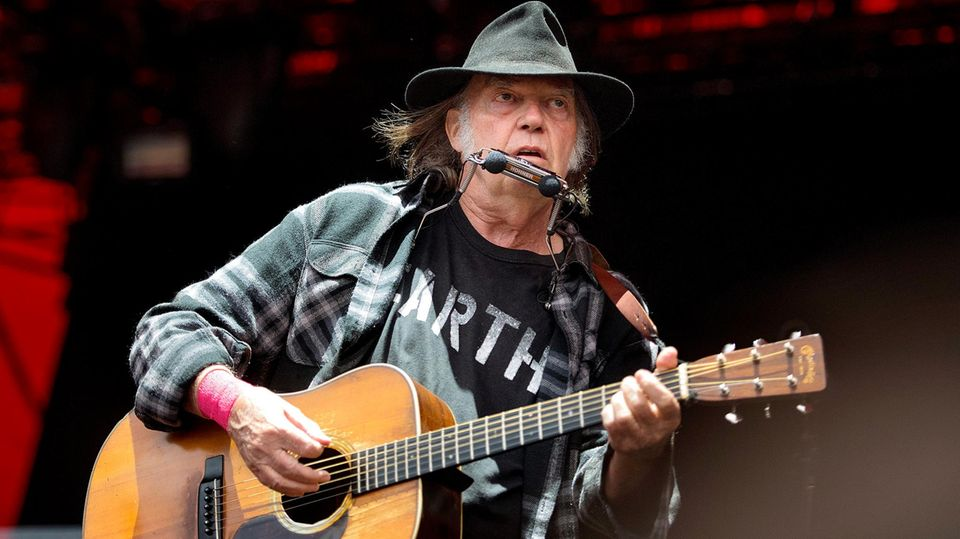 Neil Young mit akustischer Gitarre auf der Bühne