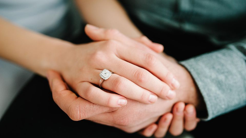 Mann und Frau halten Hände mit Verlobungsring