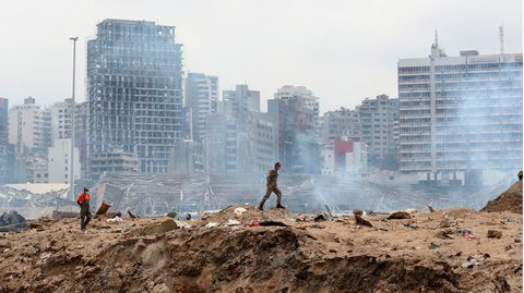 Ein Soldat geht über den Ort einer Explosion im Hafen, während im Hintergrund schwer beschädigte Gebäude zu sehen sind