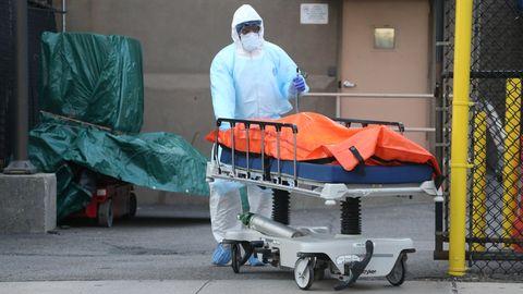 Ein Krankenhausmitarbeiter in Schutzkleidung schiebt eine Trage