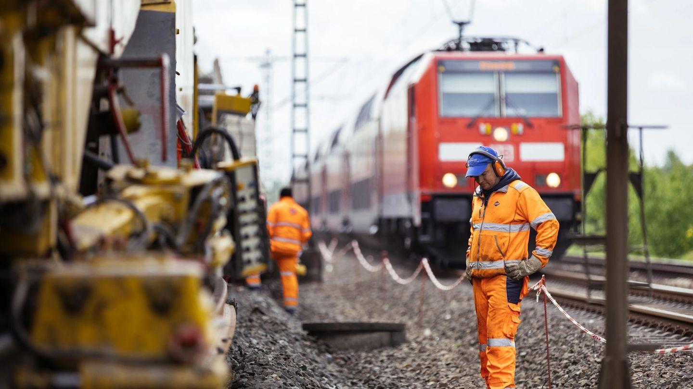 Gleisbauarbeiter sanieren eine Strecke, während nebenan der Betrieb weiter läuft