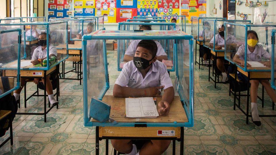 Schüler in Thailand sitzen mit Maske in einem Plastikkubus an ihren Plätzen