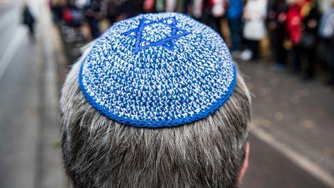 Ein Mann mit Kippa steht vor der Neuen Synagoge in Berlin vor einer Menschenkette