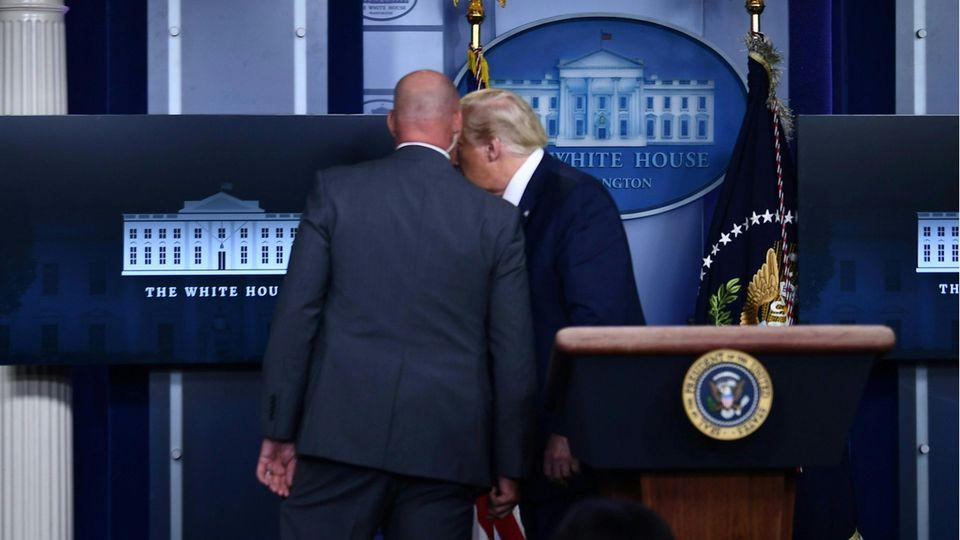 Ein Mitarbeiter des Geheimdienstes holt Donald Trump aus dem Briefing. Kurz danach kehrte der US-Präsident zu den Journalisten zurück.