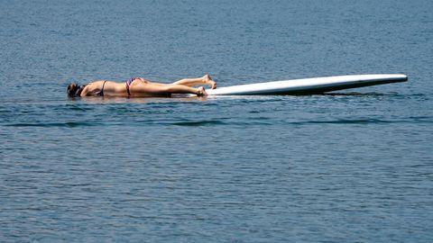 Flucht vor der Hitze:Eine junge Frau liegt im Riegsee auf einem Surfboard
