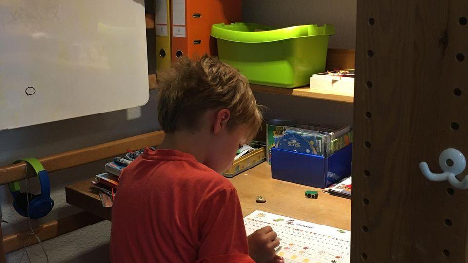 Der siebenjährige Peter lernt an einem kleinenSchreibtisch, der unter seinem Hochbett steht