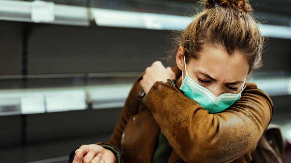 Coronavirus asymptomatische Infektion: Eine Frau hustet in den Ellenbogen