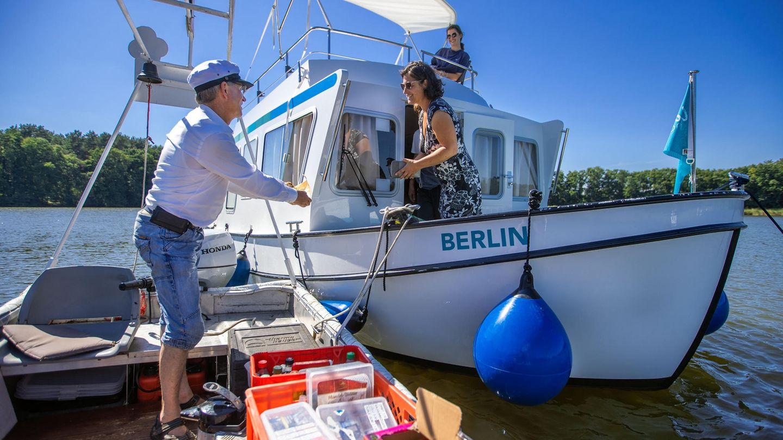 Jens Winkelmann ist mit seinem Wasserkiosk auf dem Vilzsee unterwegs und verkauft geräucherte Forellen an eine Urlauberfamilie